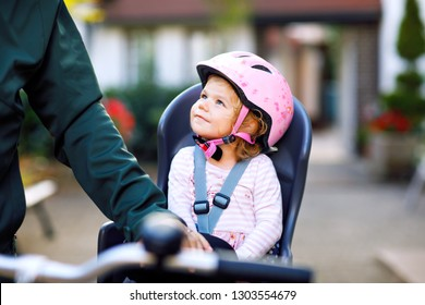 Portrait of little toddler girl with security helmet on the head sitting in bike seat and her father or mother with bicycle. Safe and child protection concept. Family and weekend activity trip.