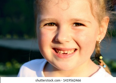 Portrait of little toothless cute girl closeup. Face of little blonde girl smiling without teeth and summer evening sun is shining on her face.