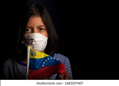 Portrait of little Venezuelan girl wearing medical mask and holding hopefully the flag of Venezuela