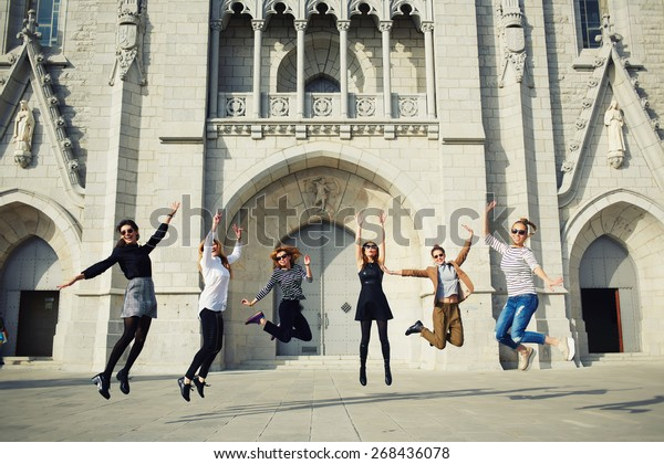 Portrait of a lively excited women jumping in air against building, enjoying holidays, group of girlfriends outdoors having lots of fun jumping around