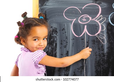 Portrait of llittle mulatto girl is drawing on a blackboard. Isolated on white background