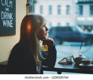 Portrait of lonely blonde woman thinking in a coffee shop and looking through the window at moody rainy city street