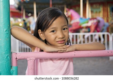 Portrait of a lonely girl at an amusement partk. Carousel at the background.