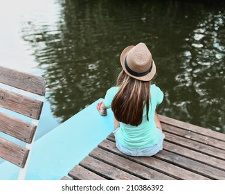 Portrait of a lonely girl in a hat near the water from the back