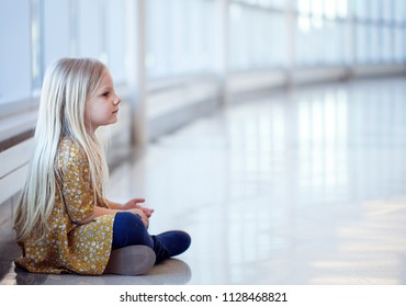 Portrait of lonely little girl in yellow dress sitting on floor