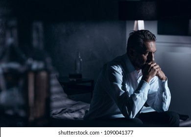 Portrait of a lonely mature man with depression sitting on a bed in a gray room with bottles of alcohol standing around