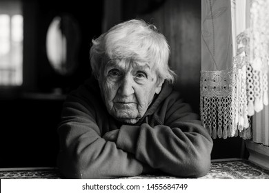 Portrait of a lonely sad old woman. Black and white photo.