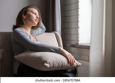 Portrait of lonely sad сaucasian young woman sitting near window of apartments.