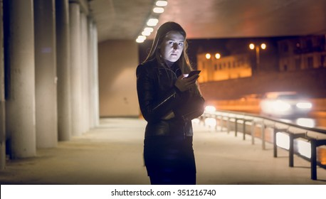 Portrait of lonely woman typing text message on the dark street
