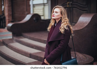 portrait of lonely young beautiful woman girl in a stylish burgundy coat standing and posing on the background of patio, courtyard, narrow street, cloudy and cold windy weather