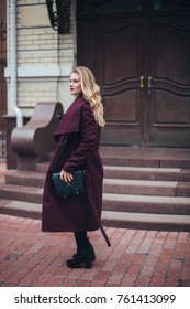 portrait of lonely young beautiful woman girl in a stylish burgundy coat standing and posing on the background of patio, courtyard, narrow street, cloudy and cold windy weather, making a step