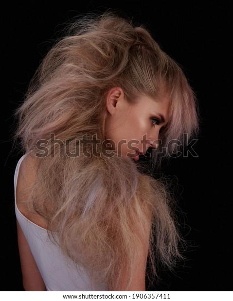 Portrait of long hair female model at black background in studio. Profile of beautiful woman with creative hairstyle. Avantgarde hair.