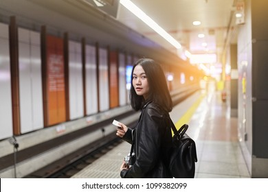 Portrait of a long hair girl wearing black leather jacket waiting for the train while holding her ticket. Young Asian woman standing near a platform with blurred metro station in background.