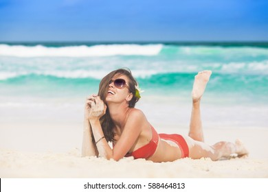 portrait of long haired woman in red bikini and sunglasses lying on tropical beach. La Digue, Seychelles