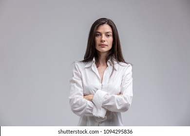Portrait of long-haired brunette woman wearing white shirt standing with arms crossed