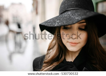 458734f49b651 A portrait of a Long-haired stylish young girl in a hat and long black
