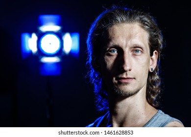 Portrait of a long-haired young man close-up. Studio portrait with colored light