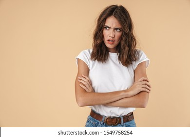 Portrait of a lovely angry young girl wearing casual clothing standing isolated over beige background, arms folded