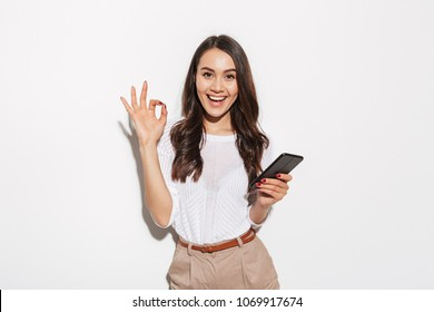 Portrait of a lovely asian businesswoman holding mobile phone and showing ok gesture isolated over white background