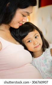 portrait of lovely asian ethnic pregnant mother and child