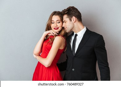 Portrait of a lovely attractive couple dressed in formal wear posing while standing and hugging over gray wall background