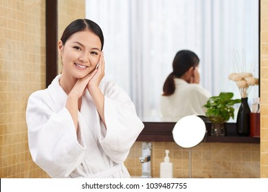 Portrait of lovely attractive woman in bathrobe smiling and looking at camera