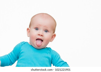 Portrait of lovely baby boy with blue eyes with tongue out, studio shot on the white background