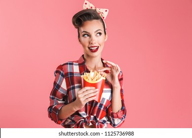 Portrait of a lovely beautiful brunette pin-up woman in headband eating french fries isolated over pink background