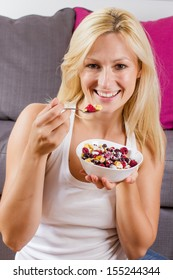 Portrait of lovely blonde woman eating cereals with fruit at breakfast.