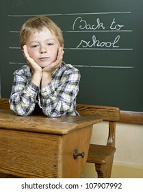 Portrait of lovely boy at school looking at camera in front of a blackboard