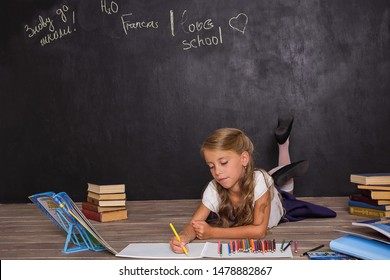 Portrait of lovely brown hair pupil lying near the school board and drawing by the pencil. Back to school