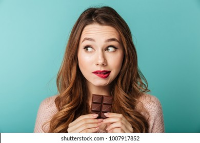 Portrait of a lovely brown haired woman with bright makeup eating chocolate bar isolated over blue background