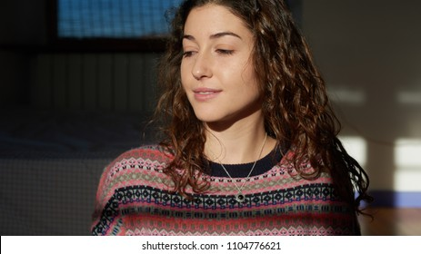 Portrait of lovely brunette girl with long wavy hair wearing small pendant and patterned sweater. She smiling in sunlight looking down.