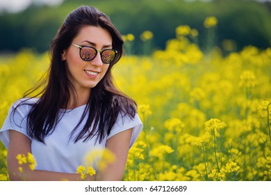 Portrait of lovely brunette in sunglasses stay in rapeseed field. Spring. Close-up.
