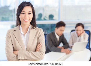 Portrait of a lovely business lady, the embodiment of enthusiasm and success, her colleagues working in the background