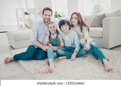 Portrait of lovely cheerful family with two kids in casual outfits sitting on carpet near sofa in modern white livingroom looking at camera. Domicile domestic lifestyle rest relax leisure concept