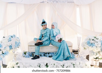 Portrait of lovely couple in reception wedding event with decoration. Asian traditional wedding dress fashion.