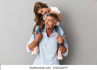 Portrait of lovely daughter smiling and sitting on the neck of her handsome father isolated over gray background