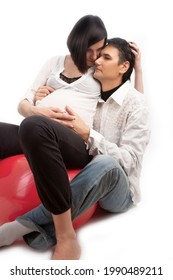 Portrait of Lovely Dreaming Caucasian Couple with Pregnant Wife Sitting Embraced Over White Background. Vertical Image Composition - Shutterstock ID 1990489211