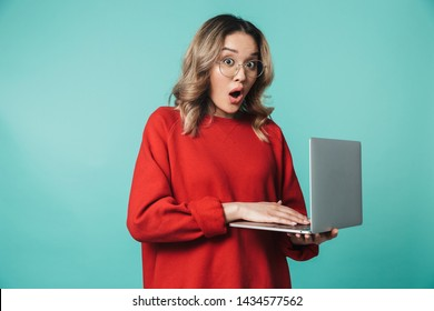 Portrait of a lovely excited young asian woman standing isolated over blue background, using laptop computer