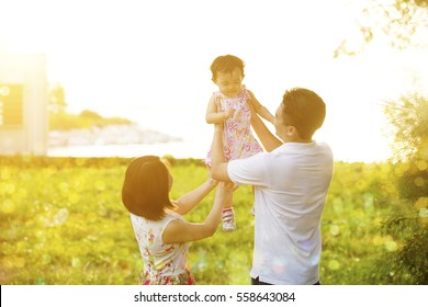 Portrait of lovely family enjoying outdoor activity together, walking on garden park in beautiful sunset during holiday vacations.