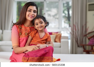 Portrait of lovely family in traditional Indian clothing sitting on sofa and looking at camera with wide smiles