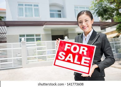 Portrait of a lovely female broker with a placard in hands