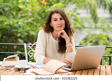 Portrait of lovely female freelance writer with a notebook sitting at her table