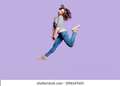 Portrait of lovely foolish girlfriend jumping in the air blowing sending kiss with pout lips having red lipstick pomade isolated on violet background, crazy people lifestyle concept