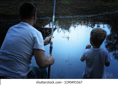 Portrait of lovely friendly father and son fishing with rods in early autumn day, happy together, family weekend concept, focus on floater
