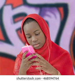 Portrait of a lovely girl adjusting a red headscarf, isolated