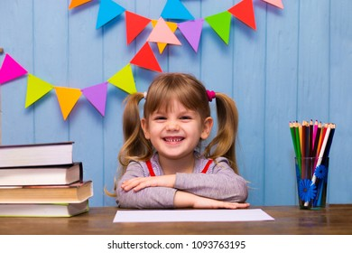 Portrait of lovely girl in classroom. Little schoolgirl sitting at desk and studying. Education and school concept - little girl with many books at school