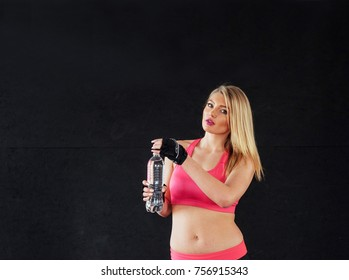 Portrait of lovely girl holding bottle of water in hand.