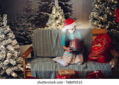 Portrait of lovely girl in Santa red hat opening box with magical light inside sitting over blanket on couch surrounded by Christmas trees in snow.